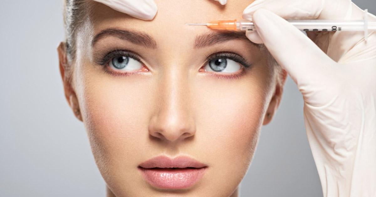 Mujer para inyección cosmética de botox en la frente.